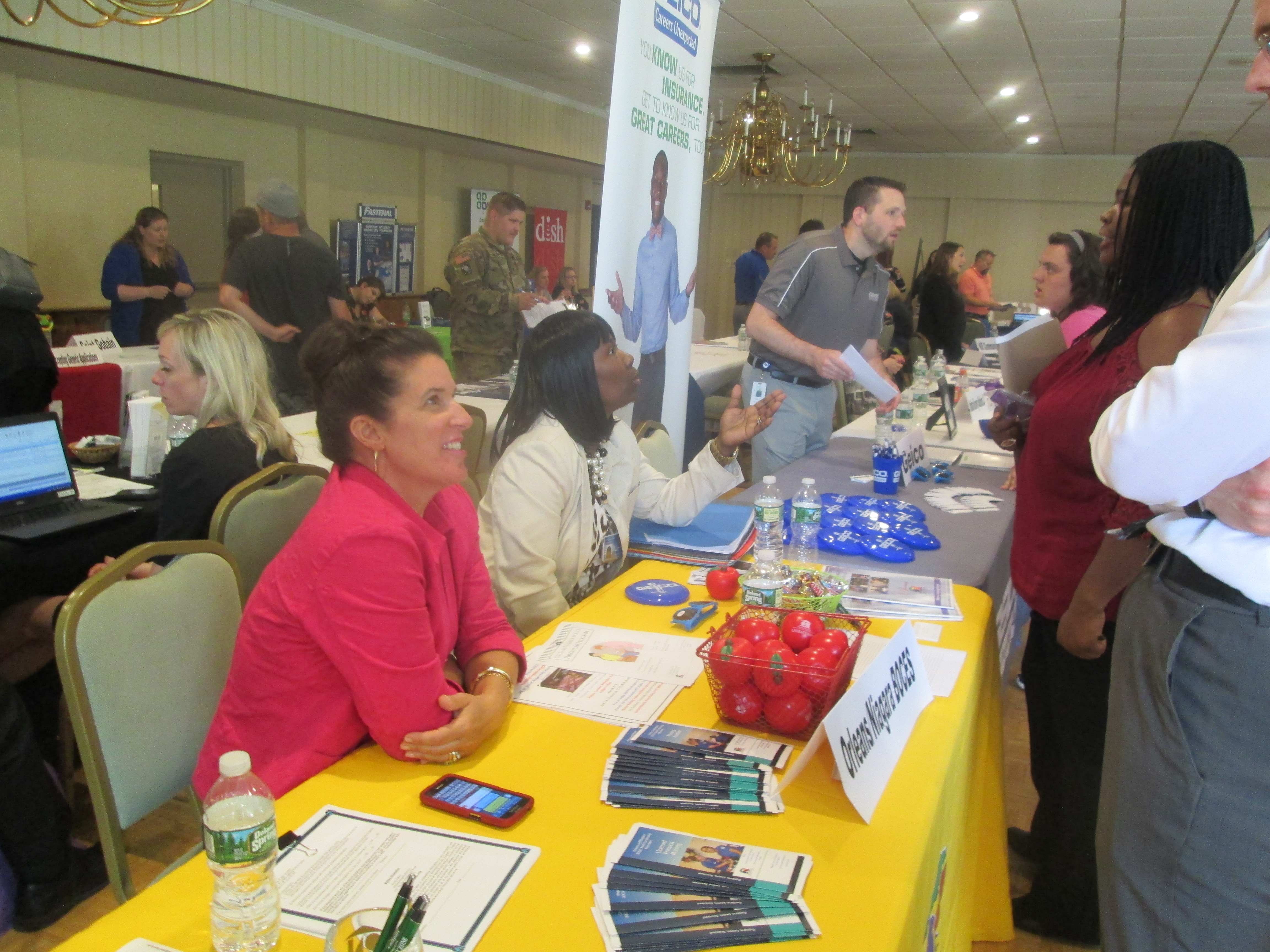 photo of career fair attendees talking with business representatives over table